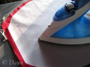 Ironing the Heat n Bond Light to the red silk for the brim