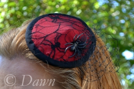 Red and black spiderweb lace fascinator close up