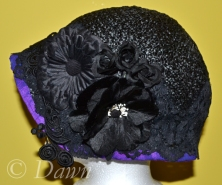 The completed black straw cloche hat decorated with black embellishments