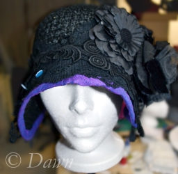 Auditioning different trims on the black straw cloche