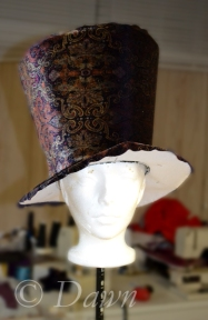 The patterned velvet band and top side of the band draped on the buckram. The lower edge of the brim will be sewn with the lining
