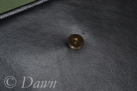 """female"" side of the magnetic snap installed into the pleather pocket"