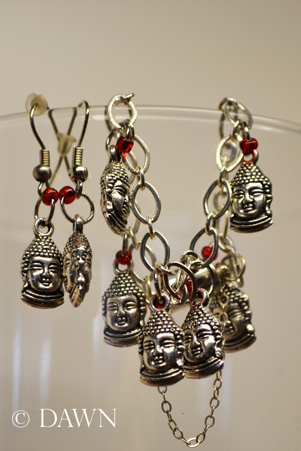 Buddha head bracelet and earrings displayed on the rim of a glass
