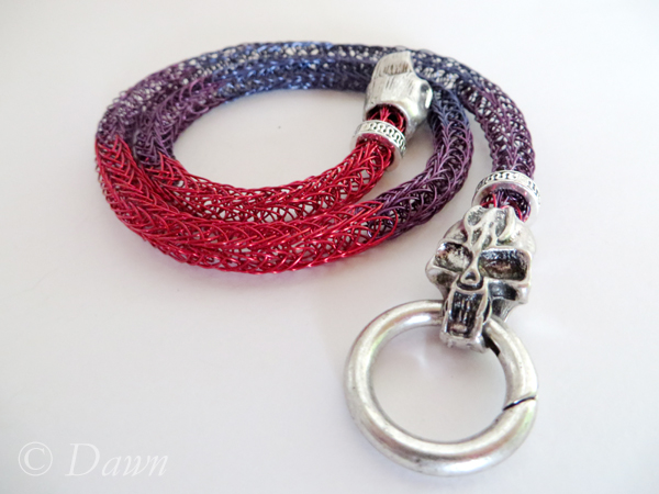 Red, purple, and blue Viking Knit with skull end caps and a spring gate clasp.