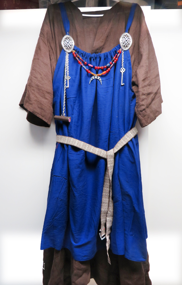 Brown linen under tunic, blue cotton apron dress with festoons, 'turtle' broaches, & 'tablet woven' belt