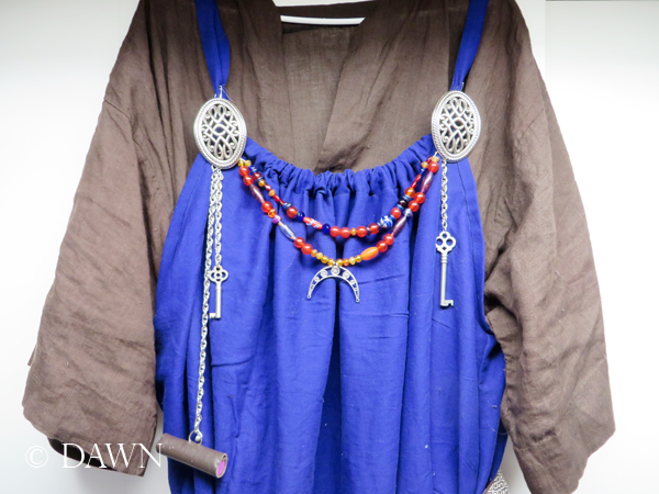 Brown linen under tunic, blue cotton apron dress with festoons & 'turtle' broaches