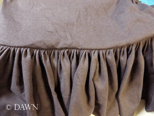 Ruffled fabric attached to skirt.