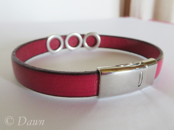 Red flat Greek leather cuff with pyramid studs and a magnetic clasp (as seen from the back)