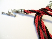 Cotton red and black Kuminimo cord (inspired by the colours of Finish metal band Turisas) topped off with horse-head terminals