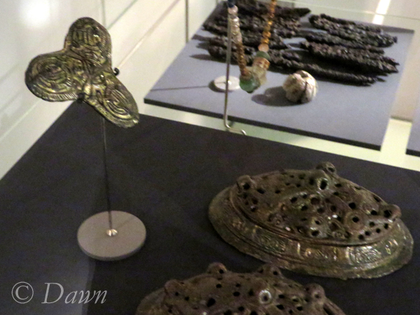 Grave goods from a Viking female grave including a tri-lobed brooch and a pair of tortoise brooches