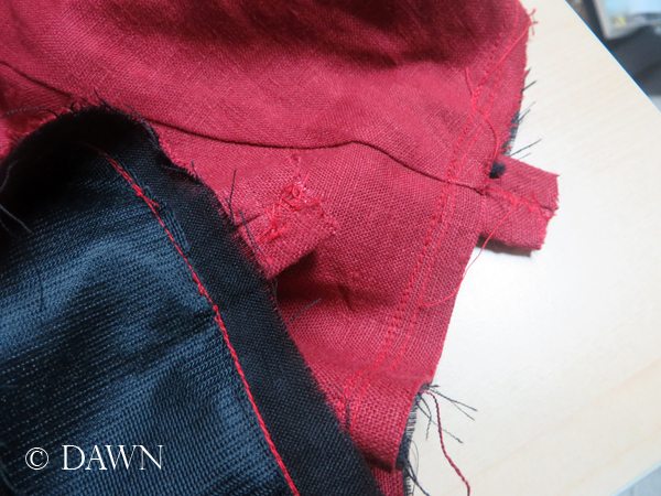 Attaching the strap loops on the red linen apron dress