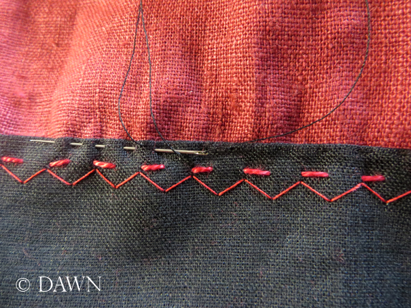 sewing the reverse facing down discreetly on the red linen apron dress