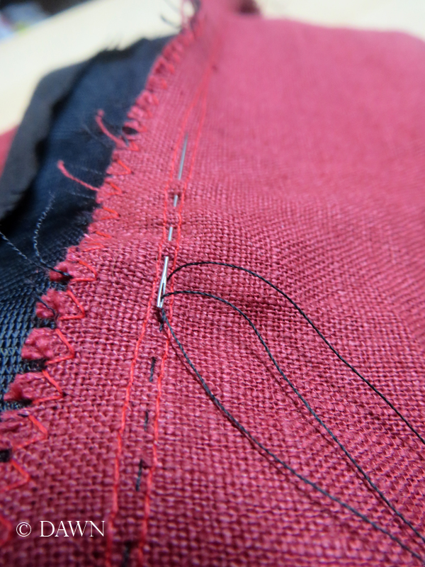 Tiny line of understitching on the reverse facing on the red linen apron dress