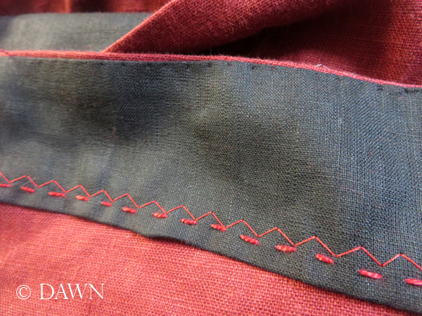 Following the machine zig-zag with a row of hand stitching on the red linen apron dress. The zig-zag will be removed.