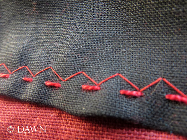 visible top-stitching on the on the red linen apron dress