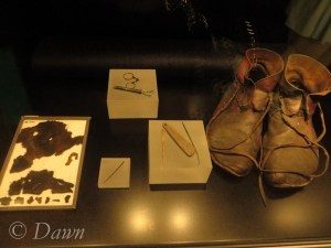 Viking 'inside the home' display at the Royal BC Museum - including a textile fragment, a pair of shoes, needles, a whetstone, and a needle case.