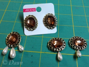 The original earrings shown with the finished brooches and a pendant ready to string.