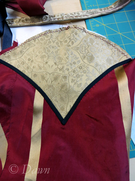 "The top of the sleeve with the gold ""shell"" added and trimmed with black bias"
