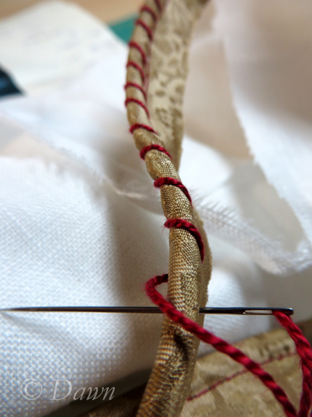 Whipping the gold piping with red embroidery thread