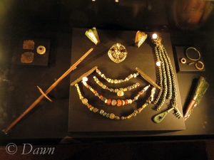 Animal-head brooches with a multi-strand necklace of beads, a drop-spindle, chains, a key, and a box brooch