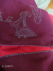Close up of the whipcord (4-strand braid), embroidered motifs, and the herringbone stitch on the reverse of the apron, with the red linen lining