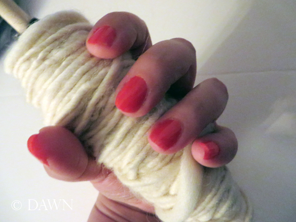 close up of the wool on the dowel, along with the orange-toned pink polish from my July ipsy glam bag