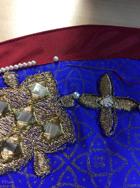 Hand-beading the collar with small fake pearls