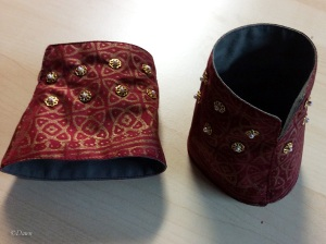assembled and embellished red and gold wrist cuffs