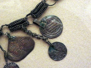 Close up on the 'triangle' pendant and nearby coins.