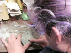 Carving the design into the soapstone