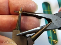 Using the tip of needle nose pliers to restore the shape of the coil edges