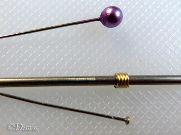 Finished smooth coil on the jig rod. Pearl head and regular pin for size guide. These are small!