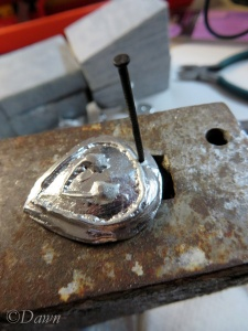 Making the hole for the bail in the heart-shaped pendant