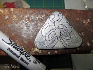 Drawing the design onto the pendant with a Sharpie