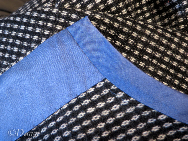 A close up of the weave and hand-finished binding done in blue silk.