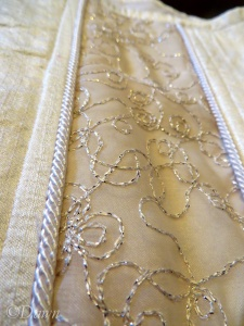 Close up of the embroidered panel and piped cord on a white silk wedding corset.