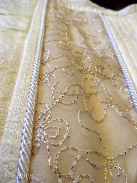 Close up of the white silk, corded piping, and the sheer embroidered fabric