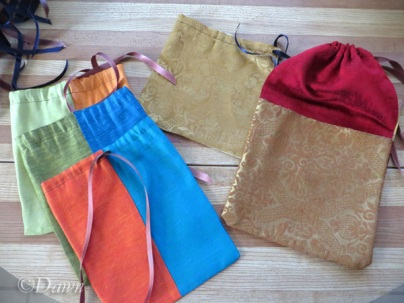 Three silk-look parti-coloured drawstring bags (left) One bag half brocade half silk-look drawstring (middle) one silk-look bag with brocade pockets also drawstring (right bottom)