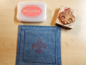 Stamping each of the fabrics with a pigment ink and fleur des lis stamp.