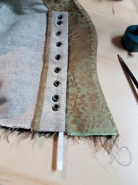 The completed lacing strip in my German renaissance bodice, sliding a piece of boning into the strip. This will support the lacing and keep the strip from buckling. It keeps tension more even.