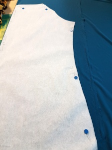 Cutting out a test garment - a blue/teal knit.