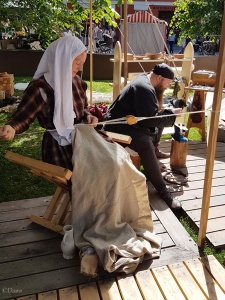 A woman doing tablet weaving, while her male companion is doing some wood working at the Turku Medieval Market