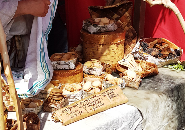 Selection of cookies and baked goods displayed in birch bark boxes for sale at the Turku Medieval Market.