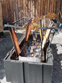 Fish nailed to a board to cook next to an open fire