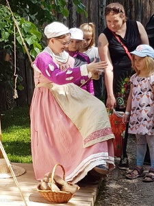 A woman demonstrating the drop spindle. She was one of the demonstrators at the Turku Medieval Market from the SCA group.