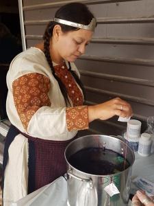 The Baroness of Borealis (mundanely Edmonton, Alberta) lowering her tied handkerchief into the indigo dye vat.