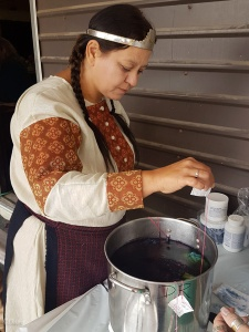 The Baroness of Borealis (mundanely Edmonton, Alberta) lowering her tied handkerchief into the indigo dye vat.