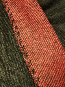 Herringbone stitch in black pearl cotton and a running stitch - on my red and black wool-blend Viking Age coat.