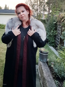 Black wool-blend coat to add to my Viking Age garb kit. This has a red and black twill reverse facing and hand embroidery using pearl cotton.