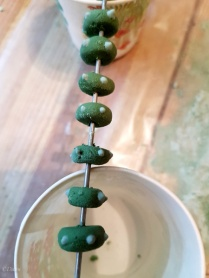 Green Egyptian Faience beads after rolling, drying on a rack before being fired in the kiln